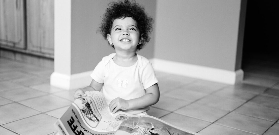 young child reading an oversize book