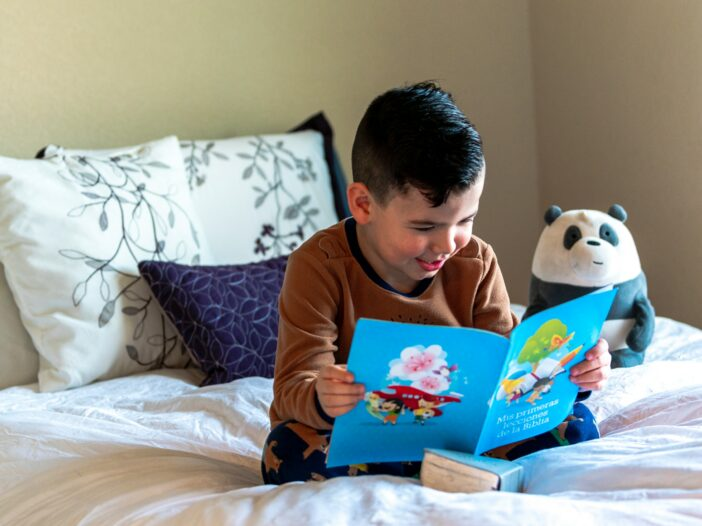 child reading a book on a bed