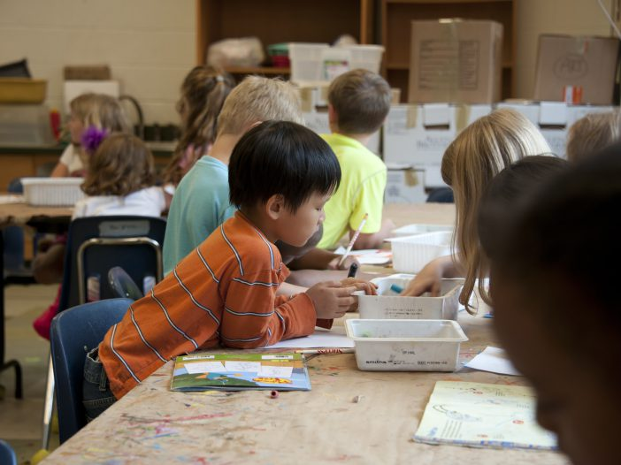 kids at school coloring together