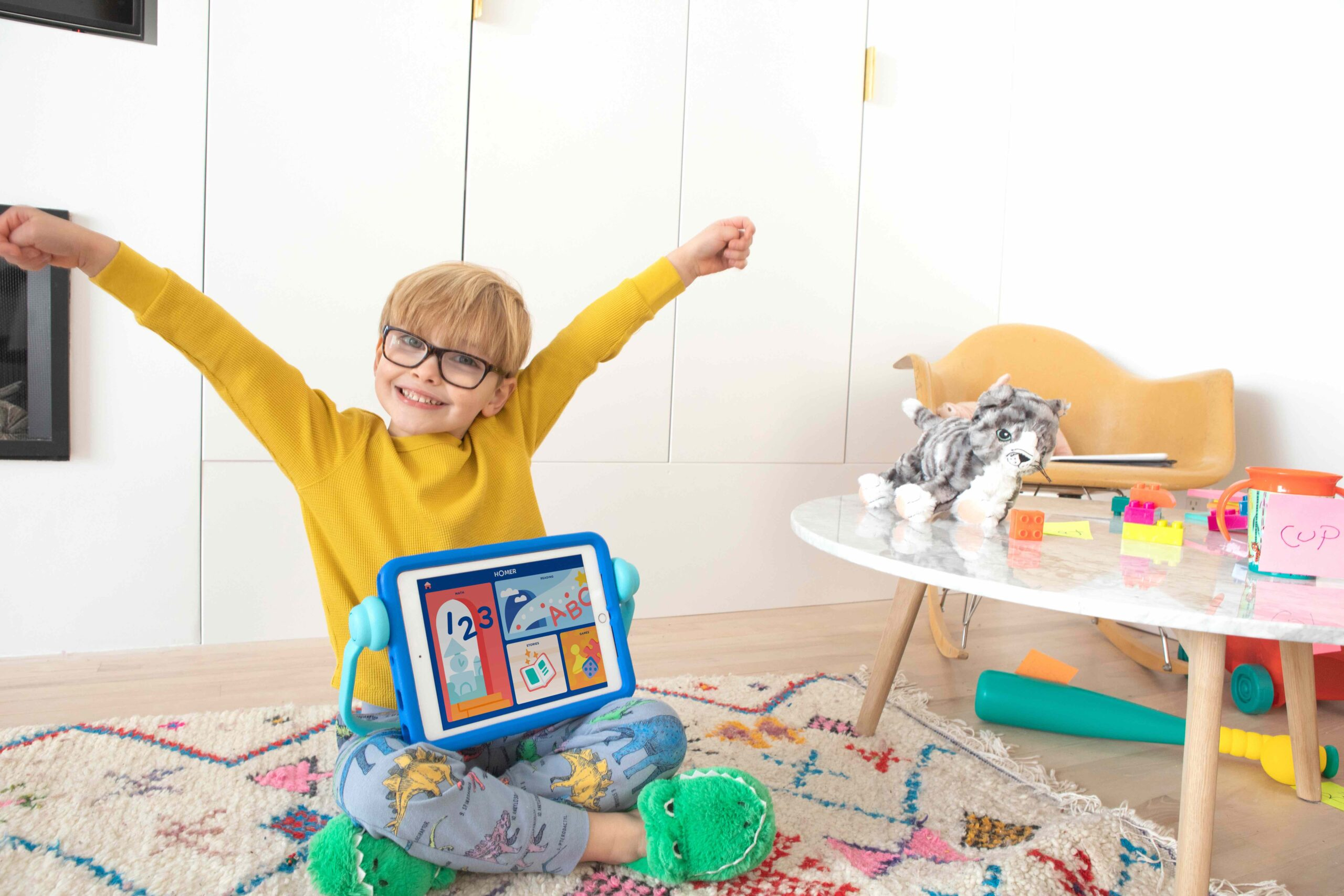 child on the floor with a reading app on this tablet