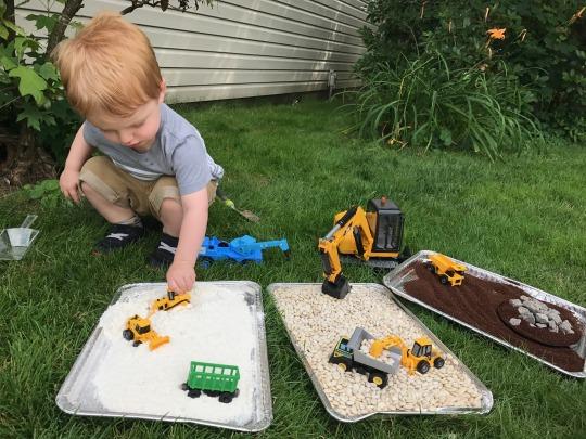 child playing with a dump truck sensory bin
