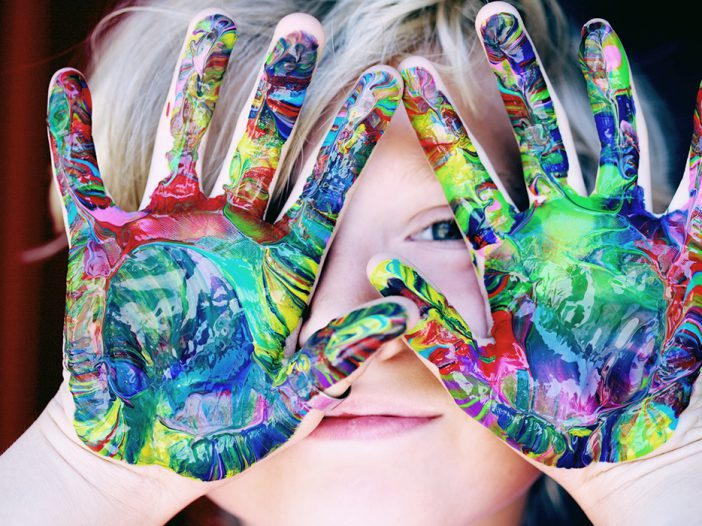 A child has their hands covered in paint, reading to make a handprint card