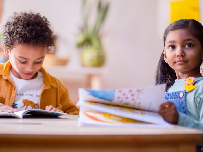 Two kids are enjoying reading together