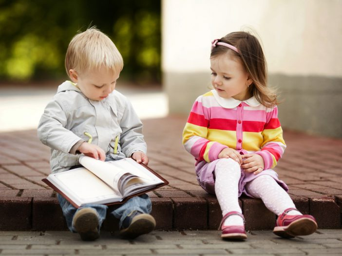 two toddlers sitting outside reading a book