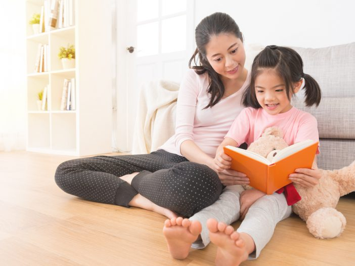 Mom reading on the ground with daughter
