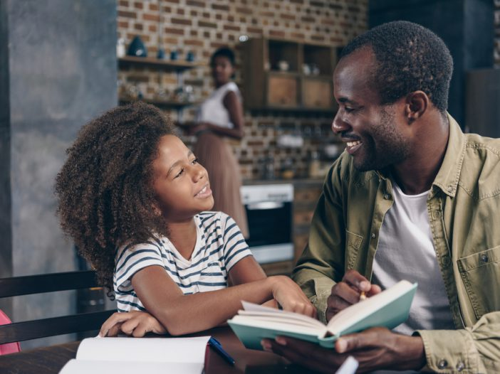Dad reading aloud to daughter