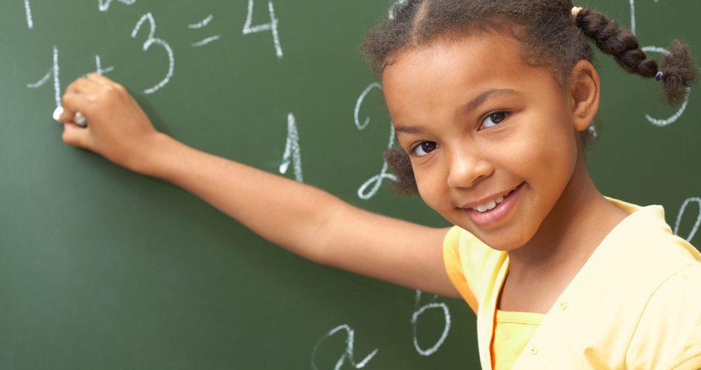 Kid doing pre-k math on a blackboard