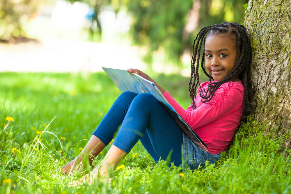 Outdoor portrait of a cute young girl reading a book