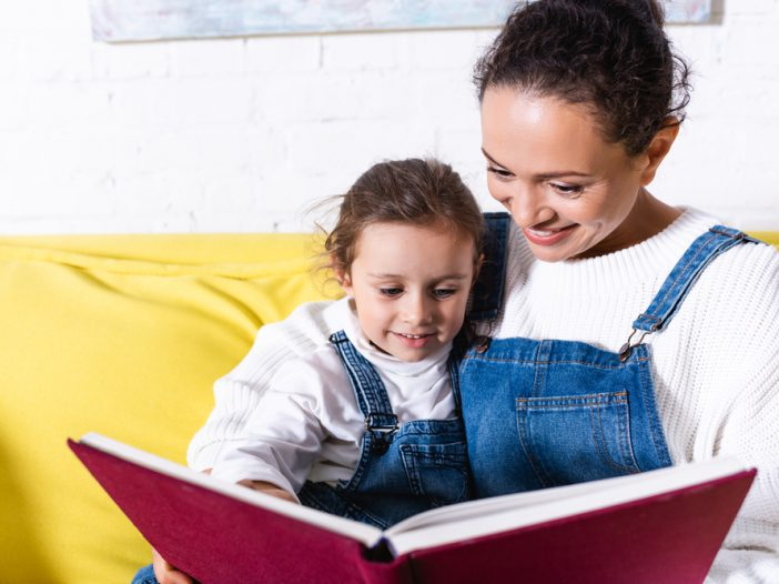 Mom sitting with child while reading a book