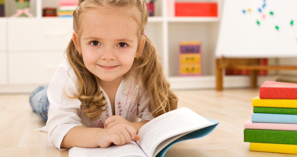 Happy little girl practicing reading laying on the floor in her room