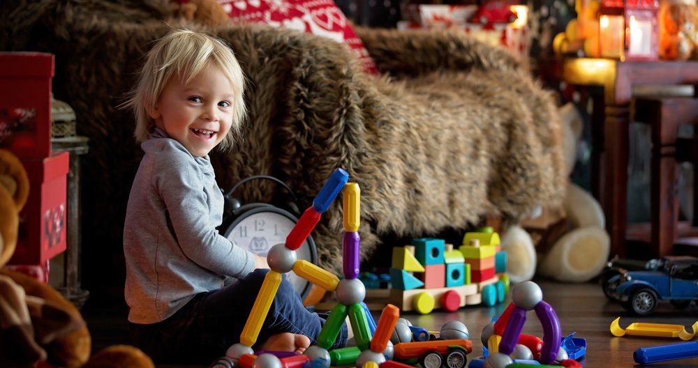 Sweet blonde toddler boy, playing with plastic construction, making different shapes,