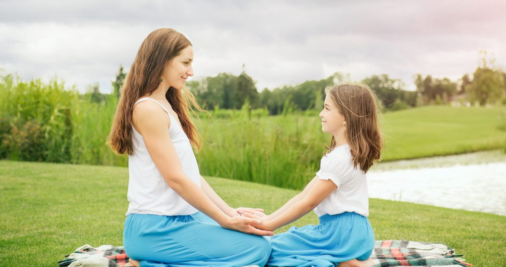 Mother with daughter teacher her meditation for kids