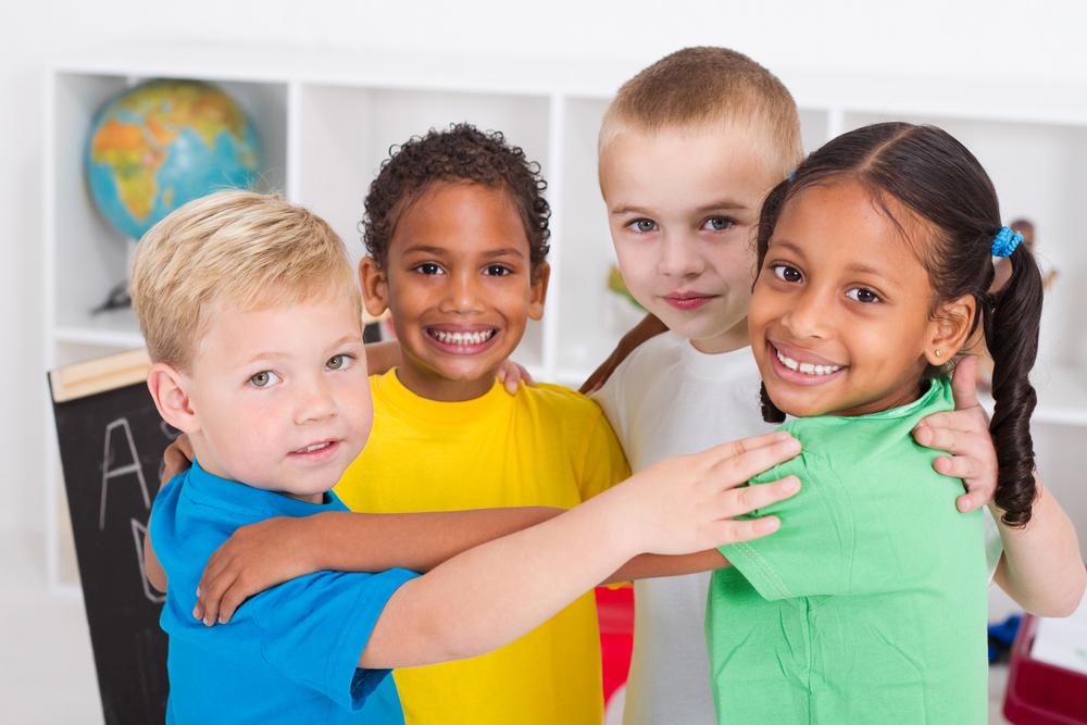 group of happy preschool kids hugging