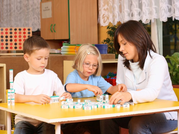teacher and 5-6 years old girl and boy learning with letters for a spelling game