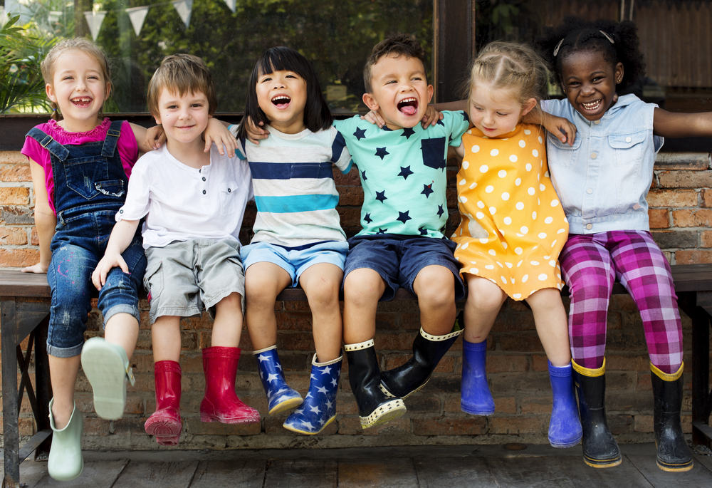 Group of kindergarten kids friends arm around sitting and smiling