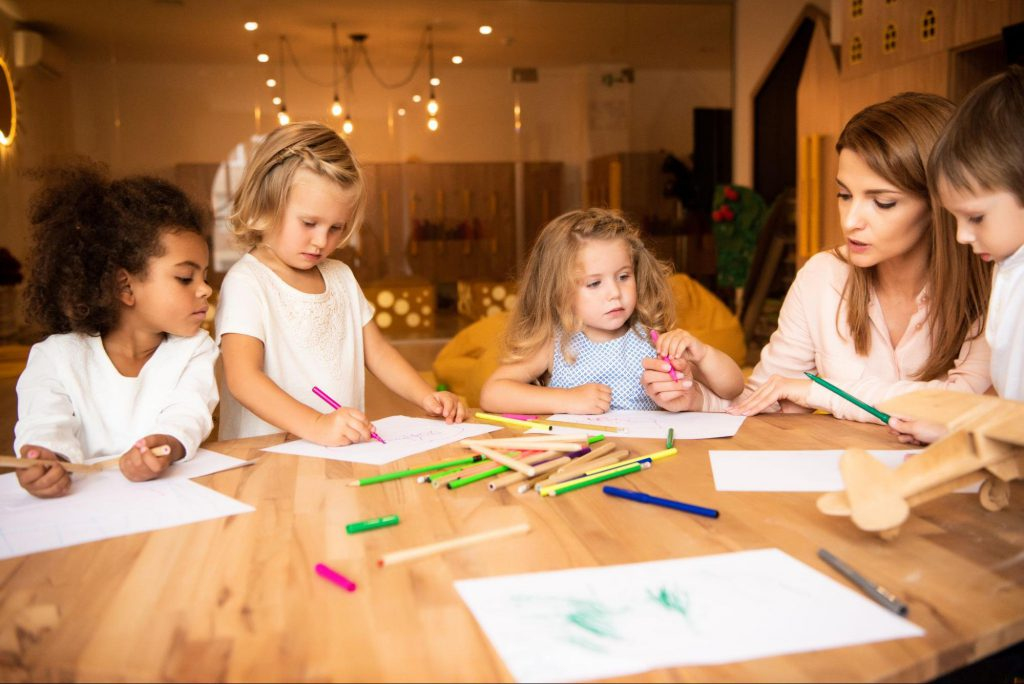 Young kids at a table coloring
