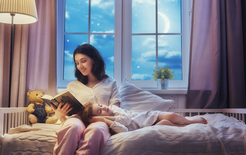 mother reading a book to daughter during bedtime routine