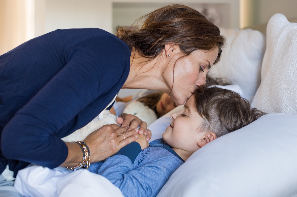 Mom kissing son on forehead as part of her kids bedtime routine