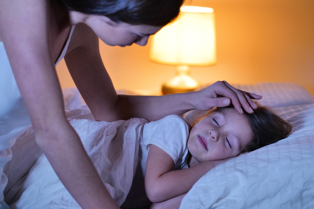 Mom checking in on child while they are sleeping