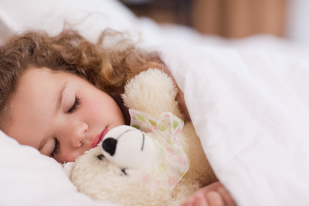 child sleeping with her teddy bear as part of her bedtime routine
