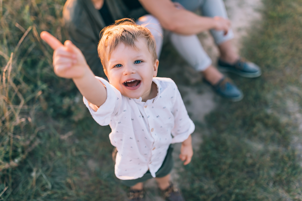 A kid pointing up with his finger