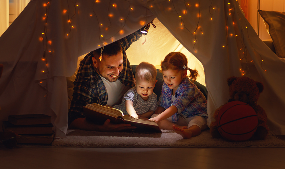 Dad reading to kids in a tent to show them calming strategies for kids
