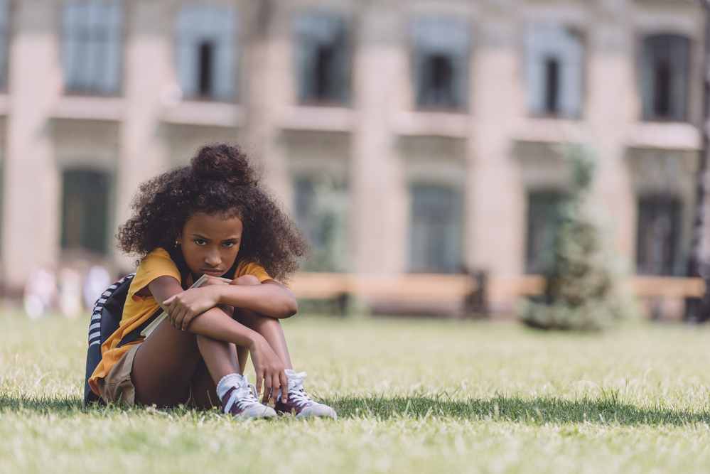 Young girl at school sitting on grass upset