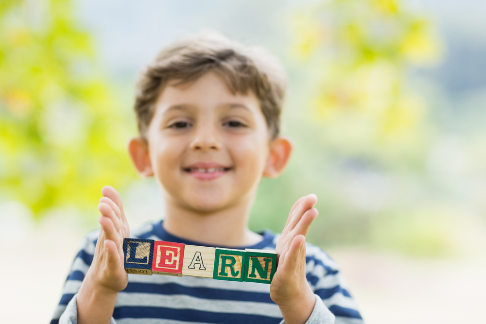 Young kid holding block letters that spell learn