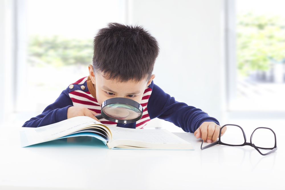 Young boy searching clues from a book with a magnifying glass