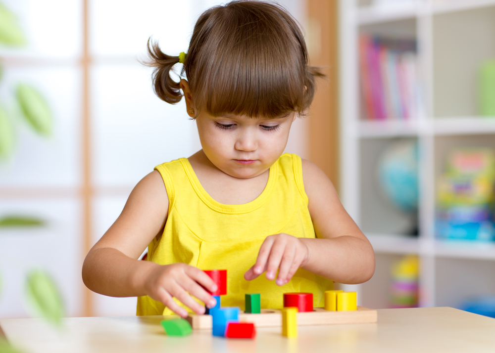 Young girl playing with shapes for kids