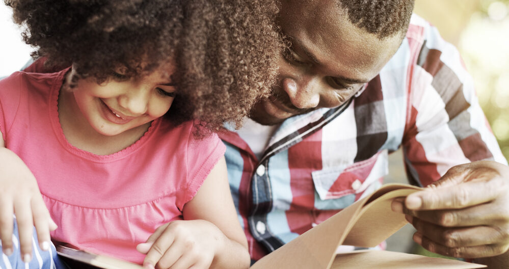 Dad helping a daughter sound out words while reading