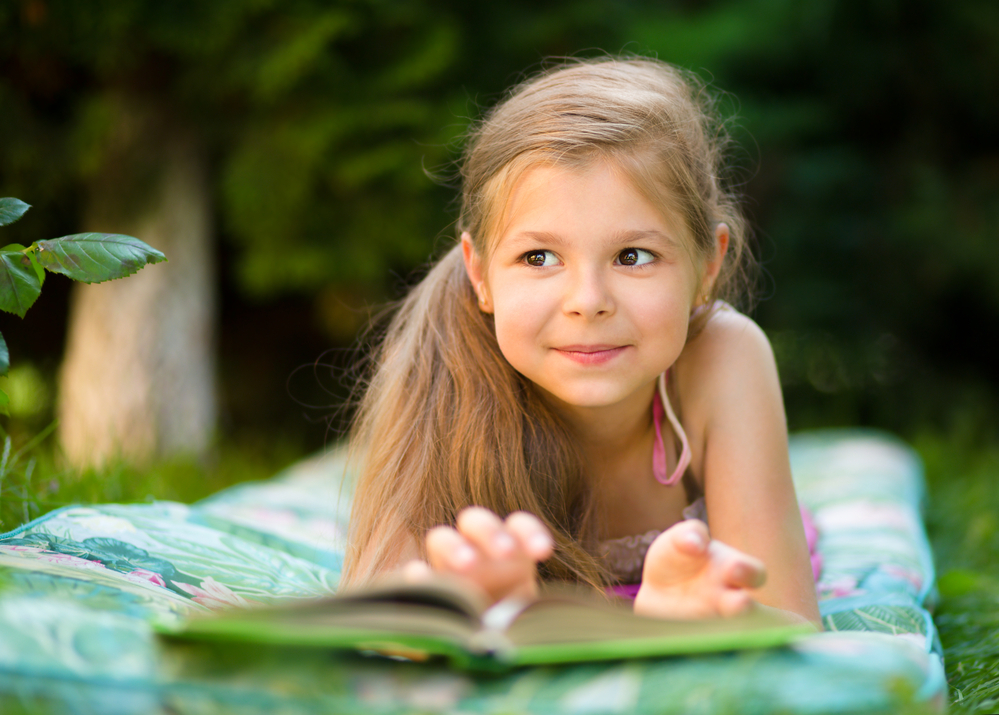 Young girl reading a book outside on a blanket