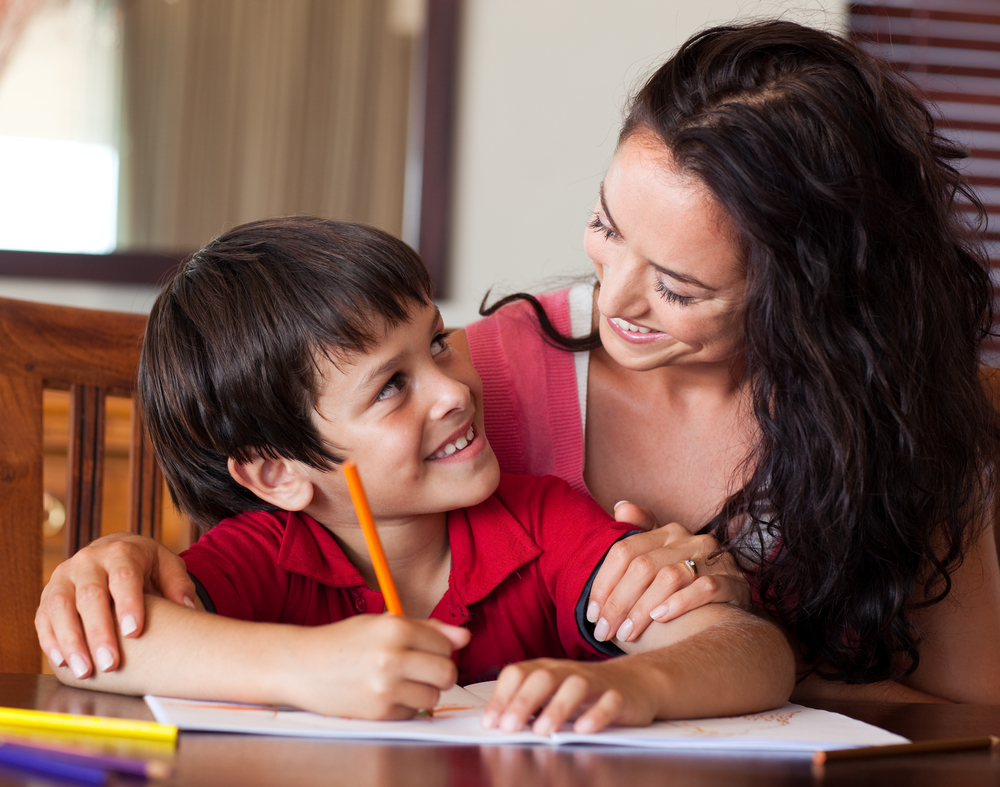 Mom encouraging her son to sound out words when writing them out