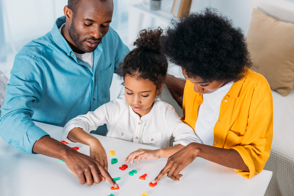 Parents playing with plastic numbers to help child learn