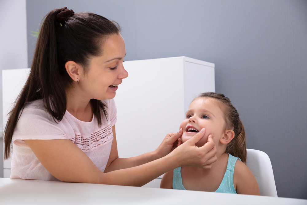 Parent helping girl to pronounce vowels