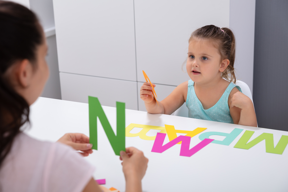 Young girl learning her vowels with cardboard letters