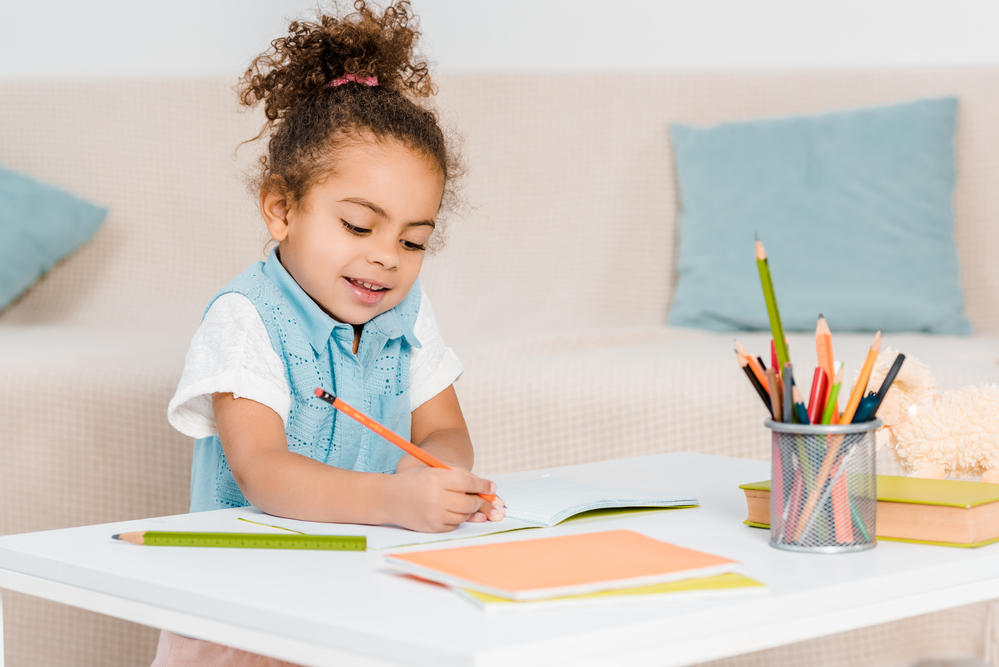 Young girl writing with colored pencils