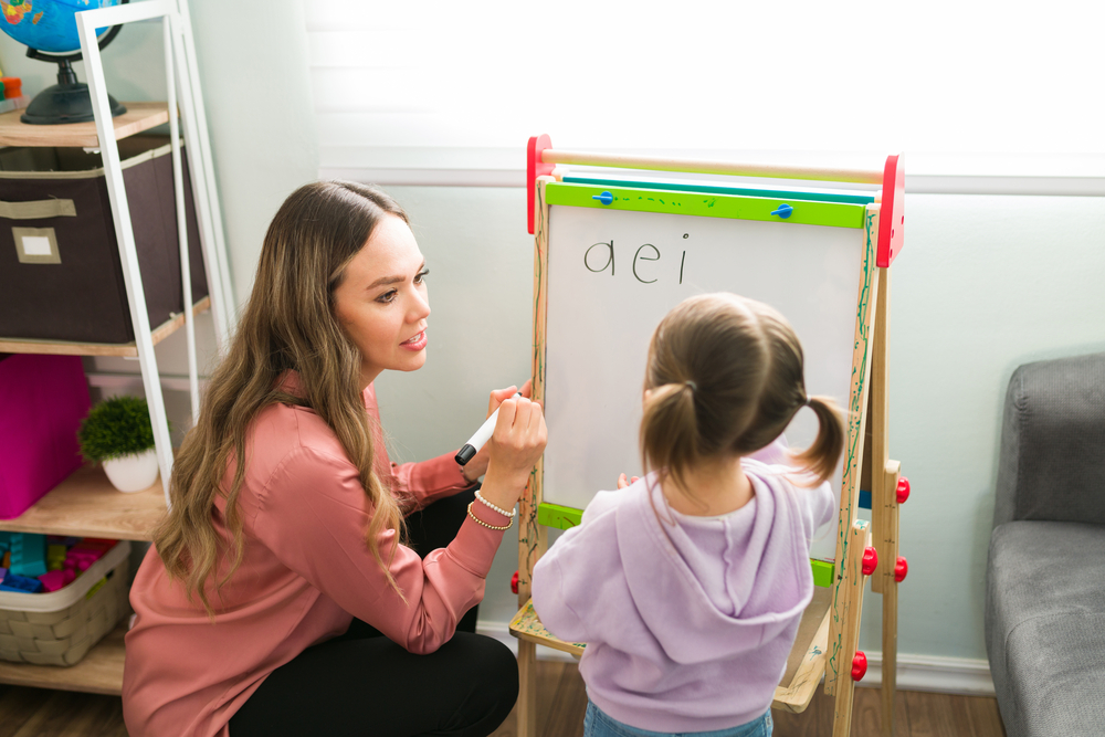 Female teacher teaching vowels to her student