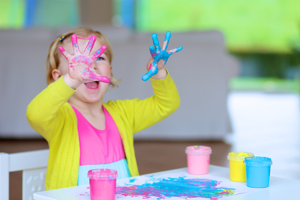 Little girl with blue and pink paint on her hands