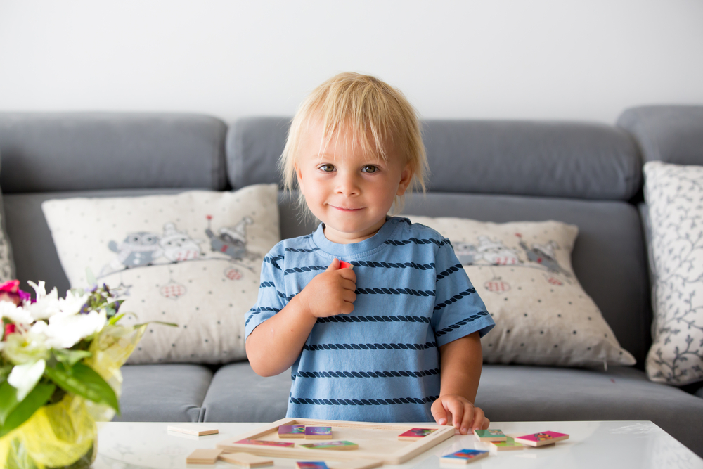 Young boy playing with a wood puzzle