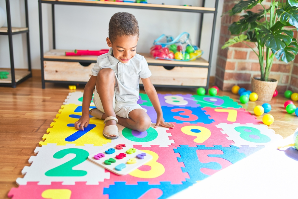 Young kid playing with wood numbers on a numbered playing mat