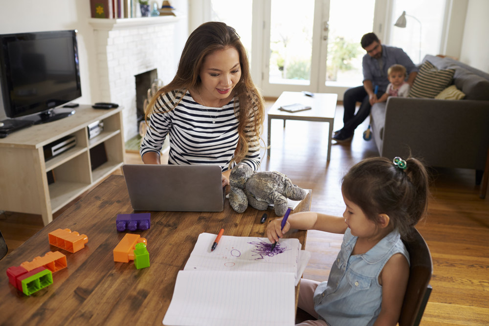 Mom searching for activities for 3-year-olds while her daughter draws