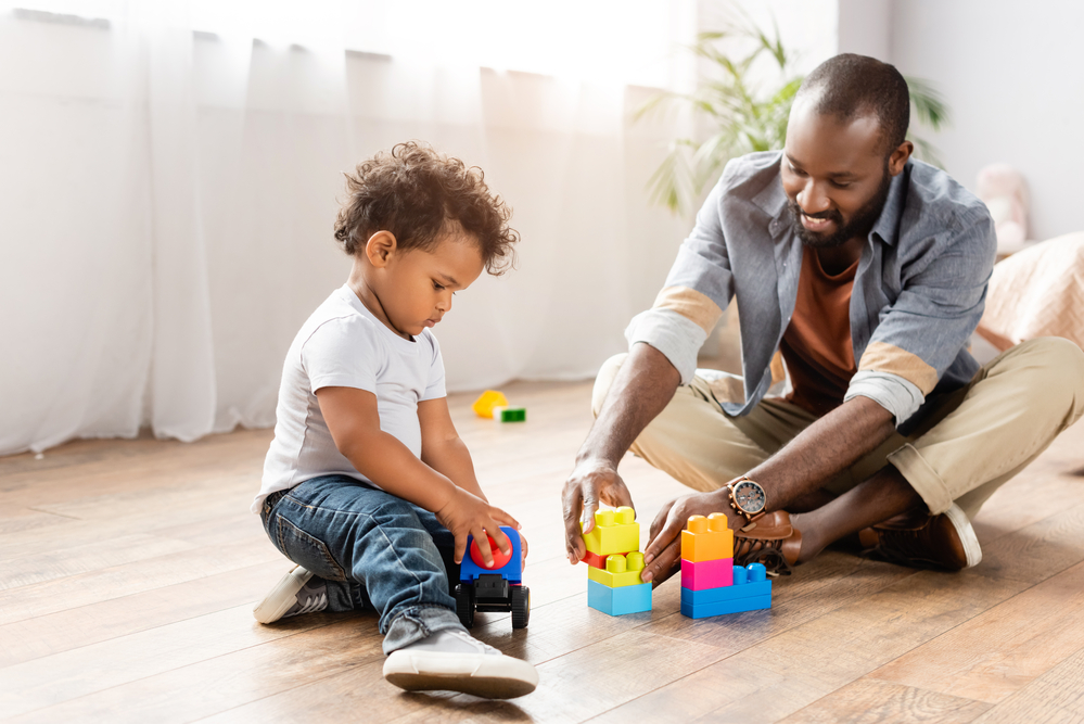 Dad playing with lego blocks with three year old son