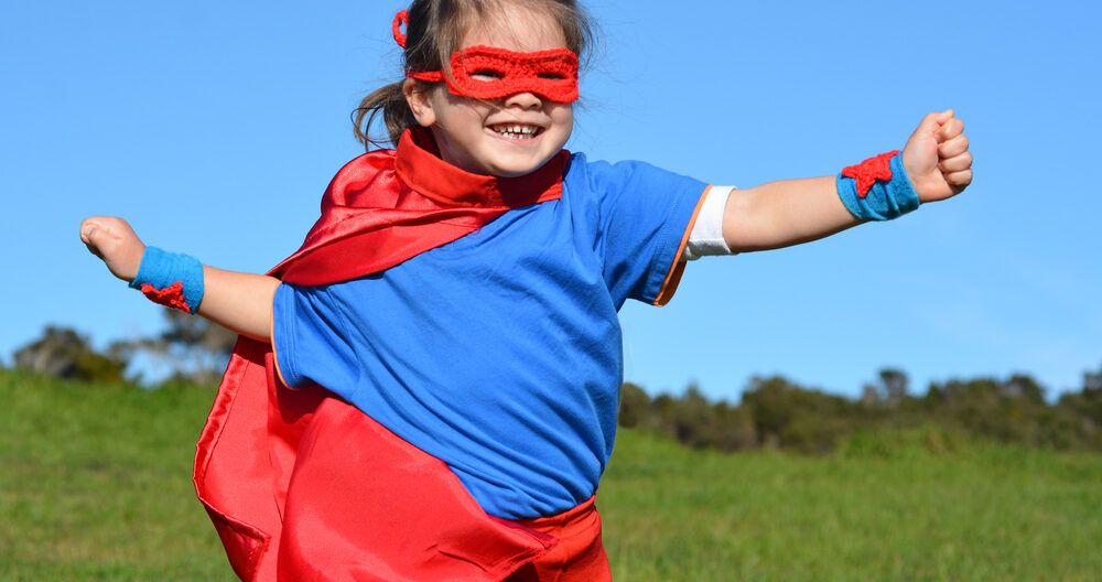 Girl dressed up as a super hero during dramatic play