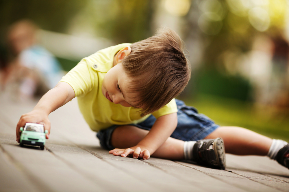 Young boy learning through play with toy cars