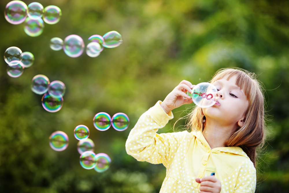 A young girl learning through play with bubbles