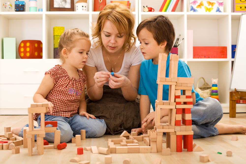 Mom helping the kids learn through play with blocks