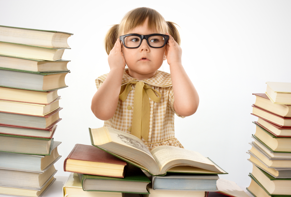 cute girl wearing glasses next to a stack of books