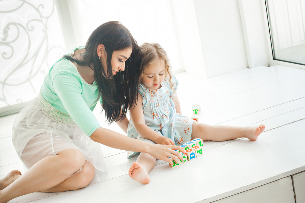 Young pretty mother studying alphabet with her little daughter