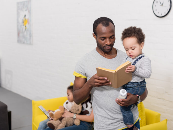 Dad hold child while reading to him